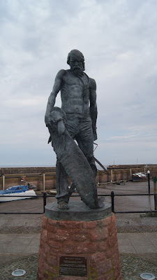 statue of man with rope around neck and holding albatross bird in front of harbour