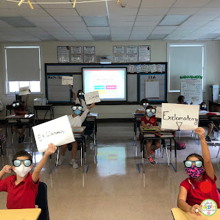 Students use their types of sentences anchor chart to help them identify the sentences displayed on the projection board.