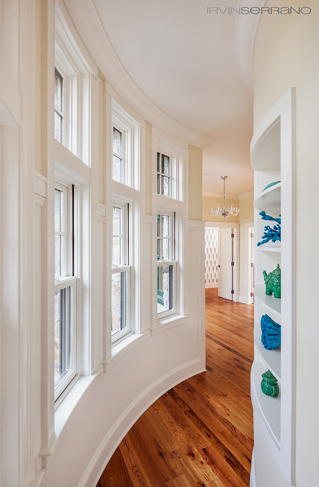 Hardwood floors and built in shelving follow the curve of a hallway in a residential oceanview home built by Bowley Builders in Maine.