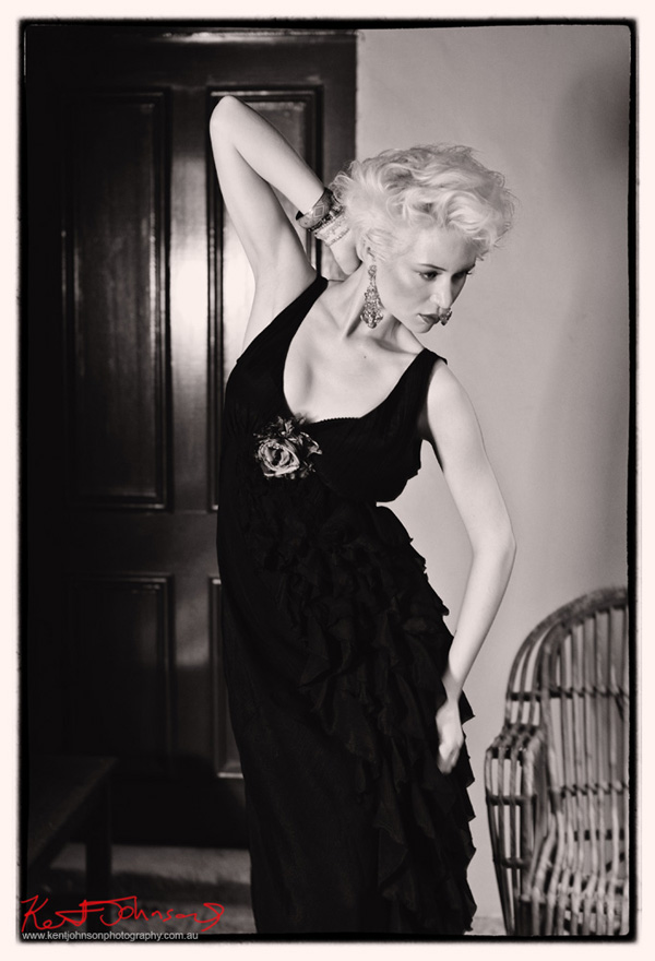 Dramatic black and white photograph of model in black dress looking like a dancer from a bygone age.  Fashion photography by Kent Johnson, Sydney, Australia.