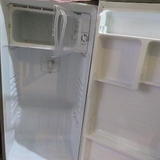 membersihkan rak agar kulkas tidak bau