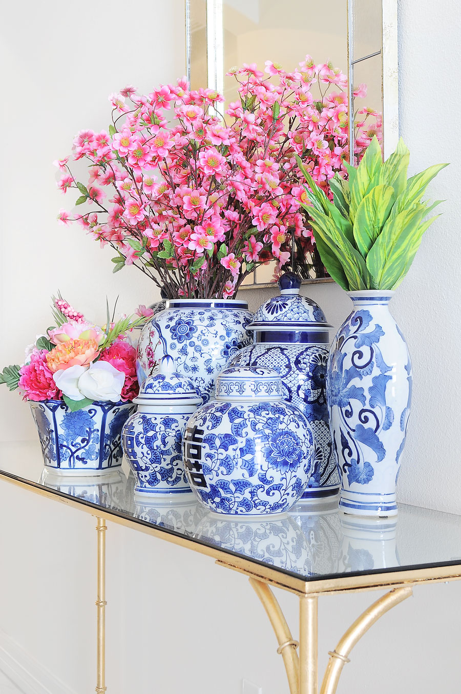 A chinoiserie collection of ginger jars and florals look chic styled on a console table in a foyer.