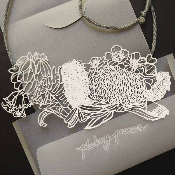 hand cut paper necklace featuring Australian native flowers in folded paper packaging