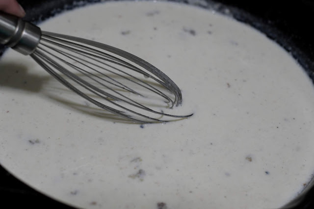 Milk being whisked into the flour, in the skillet.
