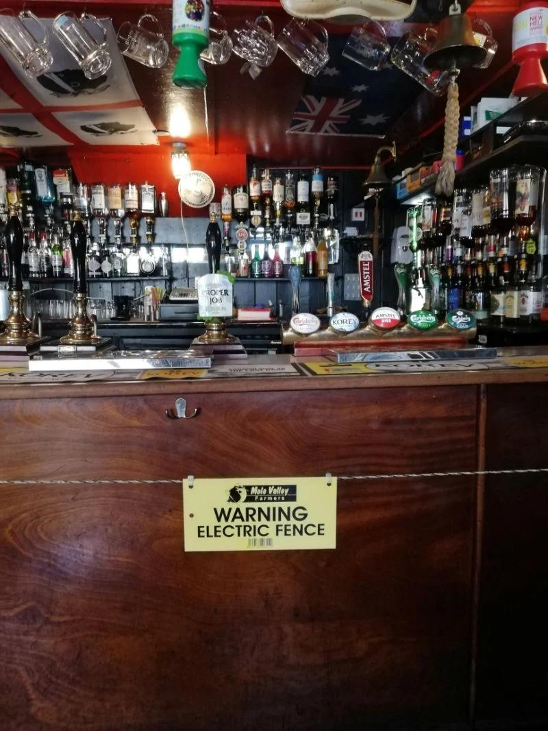 Bar pone cerca eléctrica en la barra para promover la distancia social entre los clientes y el barman