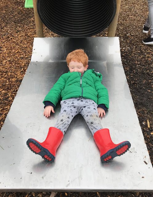 Red haired child at the end of a slide