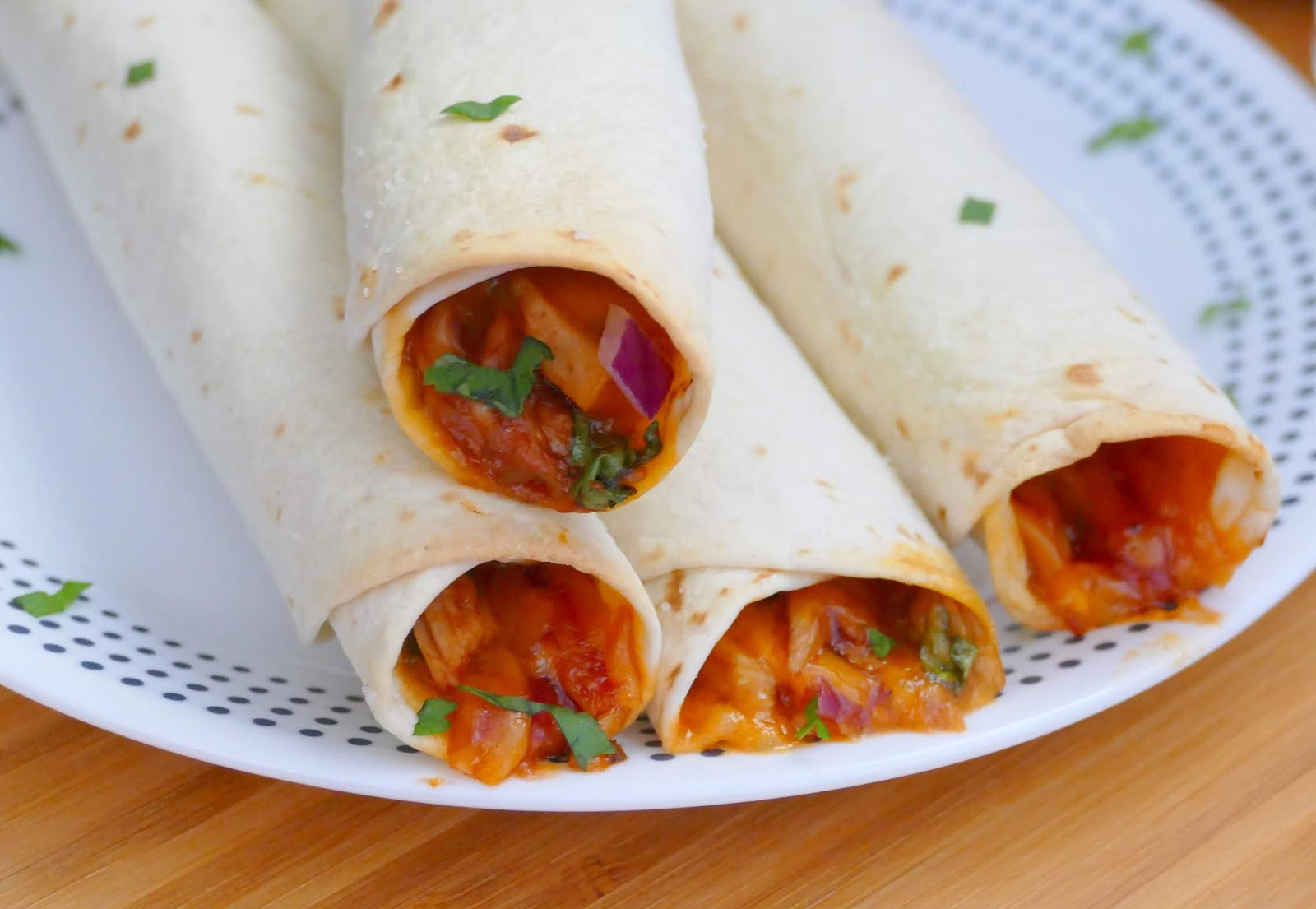 This easy baked taquito recipe is perfect as a game day appetizer, lunch or dinner! The combo of barbecue rotisserie chicken, sharp cheddar, red onion and cilantro make this a tasty treat! Give barbecue pork or beef a try instead of chicken!