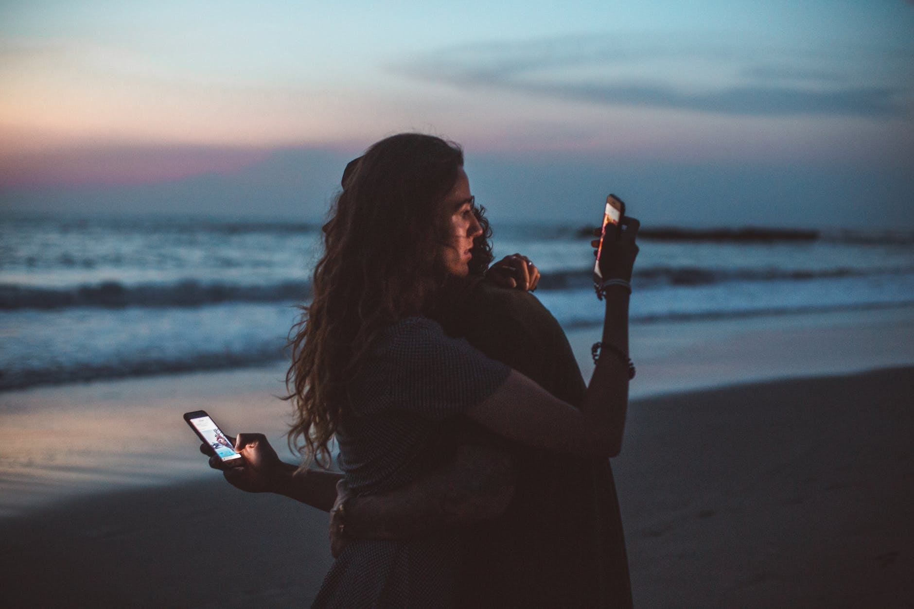 A couple hugging at the beach while staring at their phones