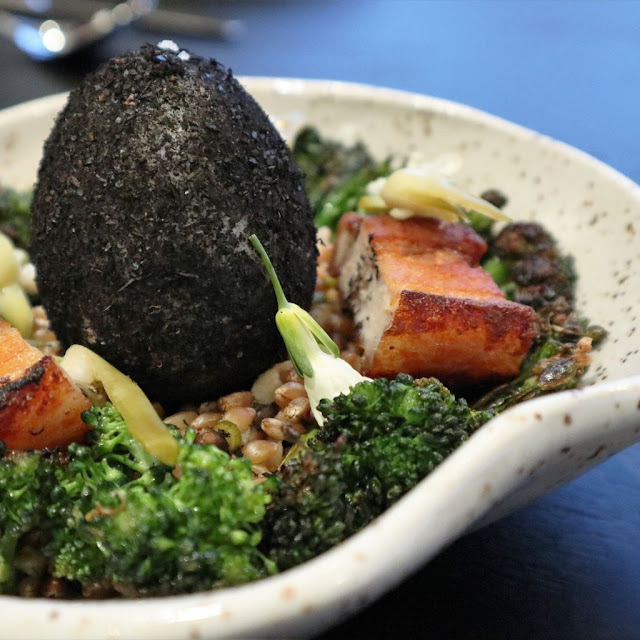 Ash covered duck egg on a bed of lentils, broccoli and pork belly