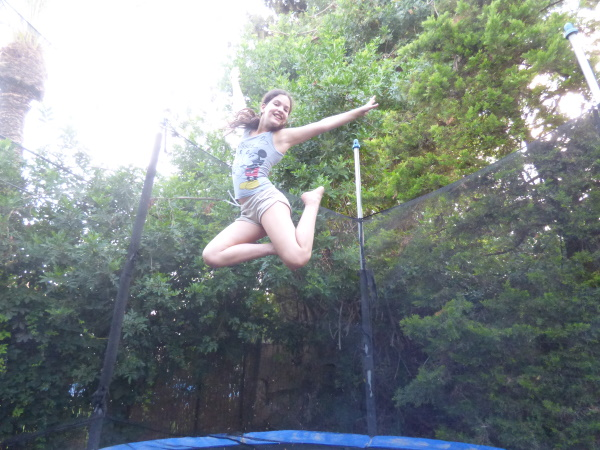 A girl jumping on a trampoline, arms stretched to her sides, legs folded to one side, smiling gleefully