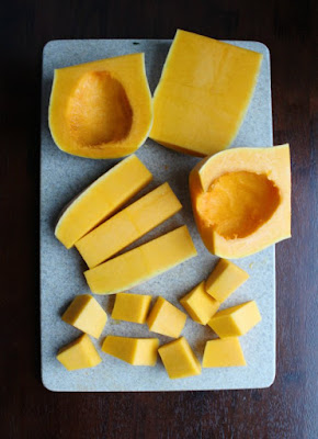 cutting board full of butternut squash pieces in various stages of being cleaned, pealed and diced.