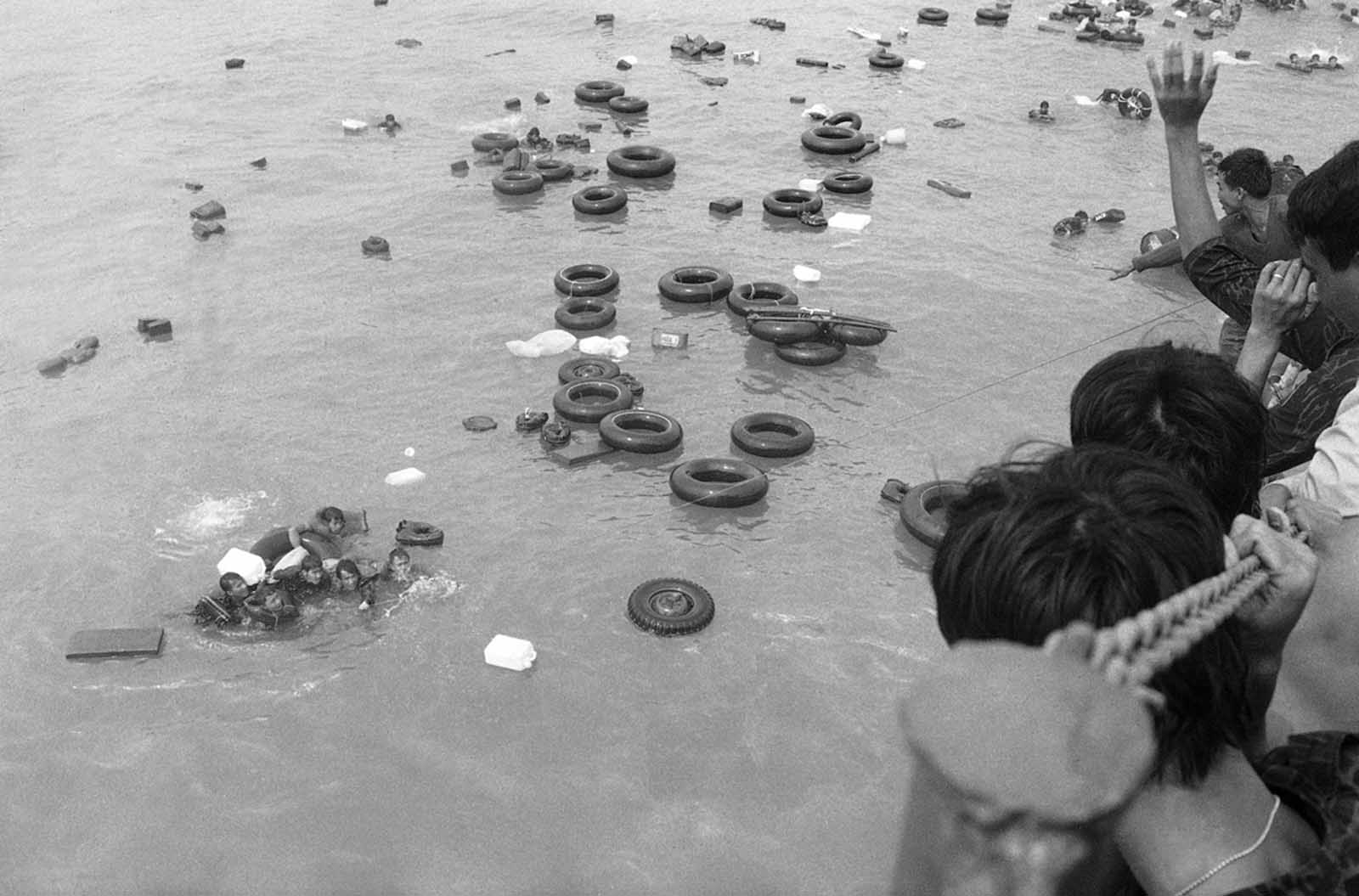 A cluster of South Vietnamese marines, some of whom unable to swim, hold onto inner tubes and empty plastic containers as buddies throw them a line to pull them aboard a navy LST off China Beach at Danang as they fled the port city in April of 1975.