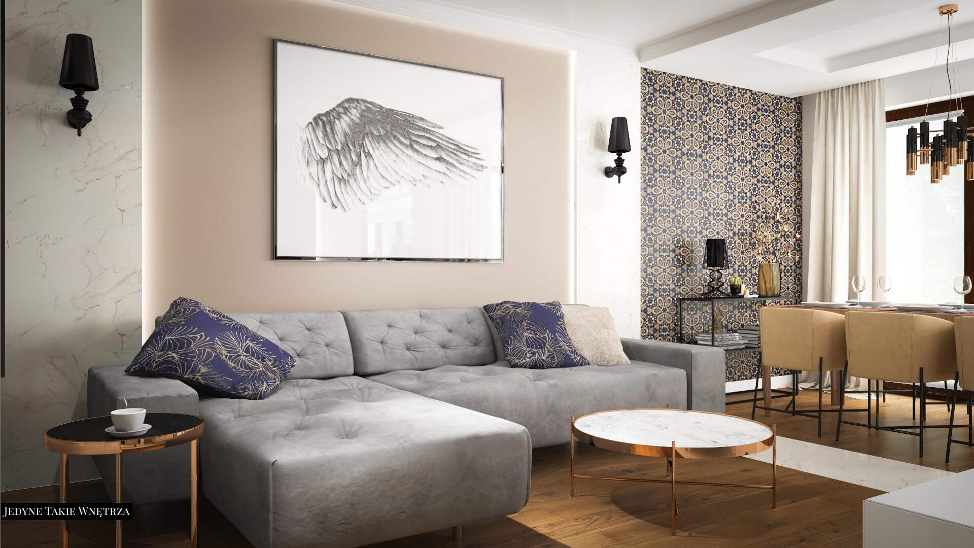 Nowoczesny salon z szarym narożnikiem. Obok stoi marmurowy stolik kawowy. Ścianę zdobi duży obraz i przysufitowe listwy.