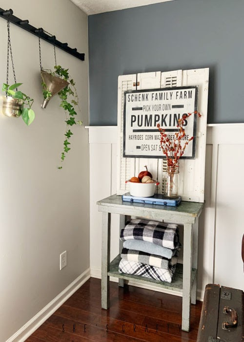 Fall Home Design on Side table with blankets on bottom shelf.