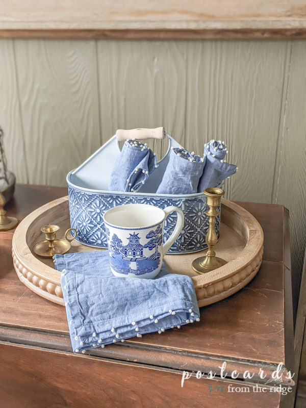 blue willow coffee mug and blue napkins on beaded wooden tray