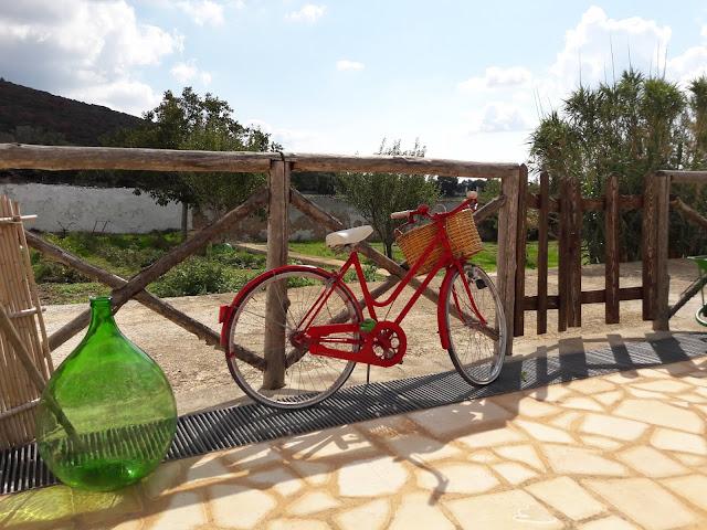 Una bicicletta rossa è appoggiata al parapetto in legno.