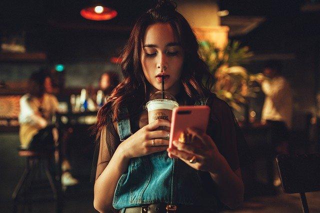 Wanita cantik yang sedang bersantai dengan telepon genggamnya