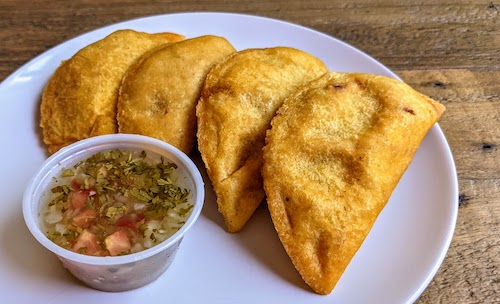 Four fried beef emapanadas with dipping sauce