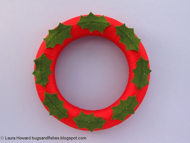 adding the felt holly leaves to the wreath