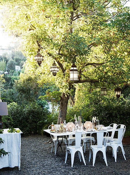 Beautiful outdoor dining in courtyard with white tolix chairs and lanterns