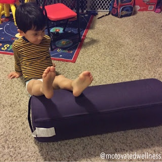 Little boy sits on the floor with his feet on a round purple yoga bolster