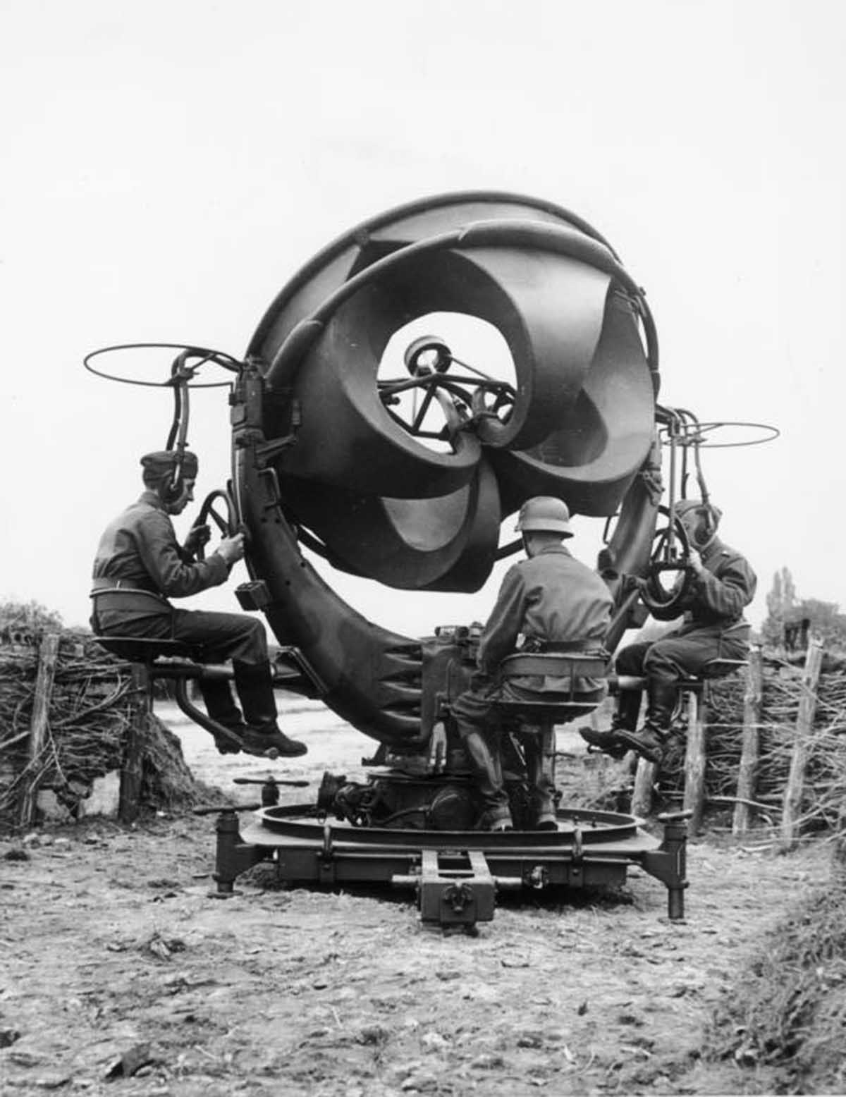 Sound location equipment in Germany, 1939. It consists of four acoustic horns, a horizontal pair and a vertical pair, connected by rubber tubes to stethoscope type earphones worn by the two technicians left and right. The stereo earphones enabled one technician to determine the direction and the other the elevation of the aircraft.