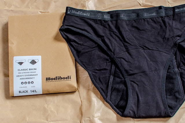 Modibodi black period pants next to the brown paper packaging. Style shown is classic bikini for heavy absorbency