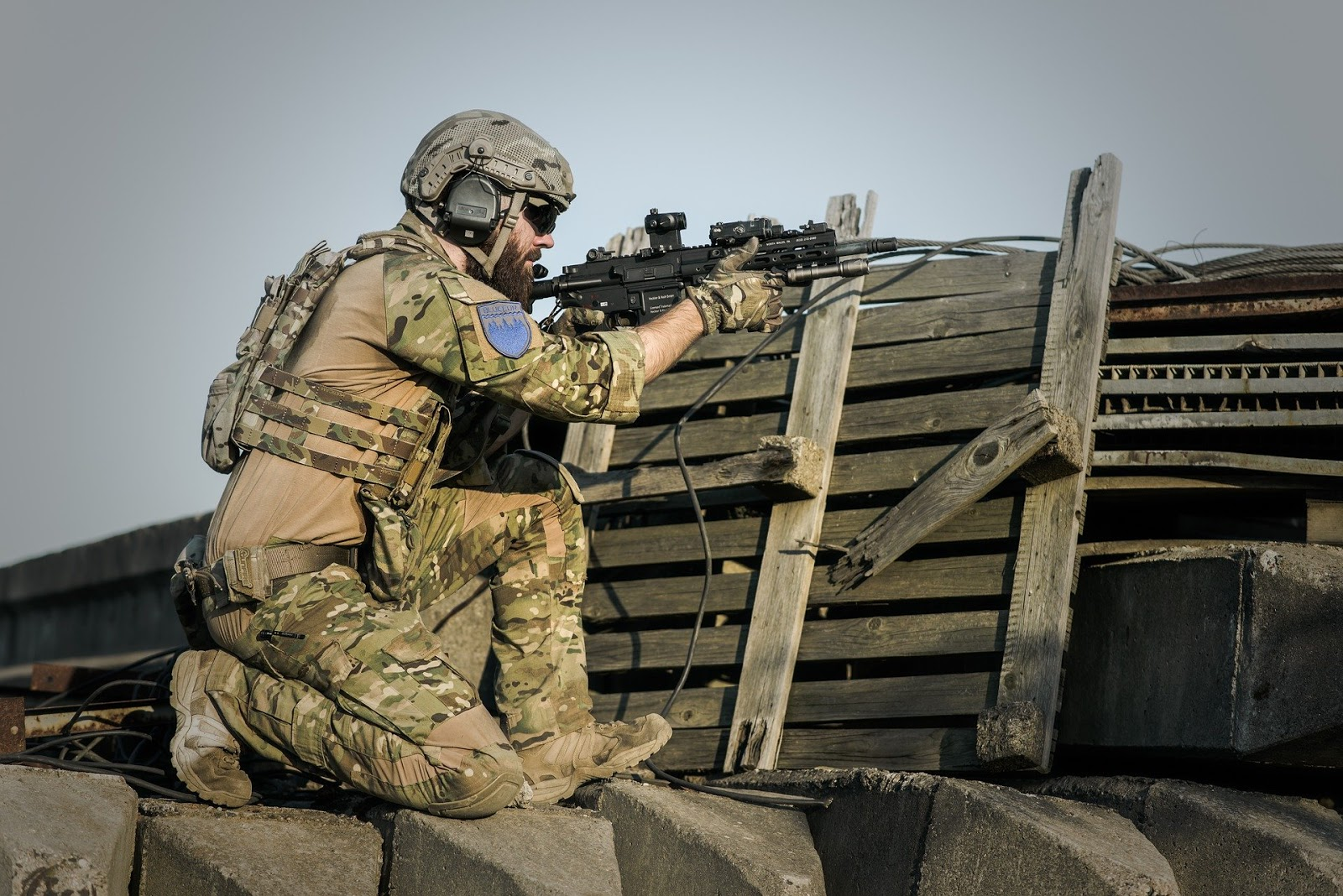army soldier kneeling behind a wall with rifle pointed at enemy for blog post about tv show Over There