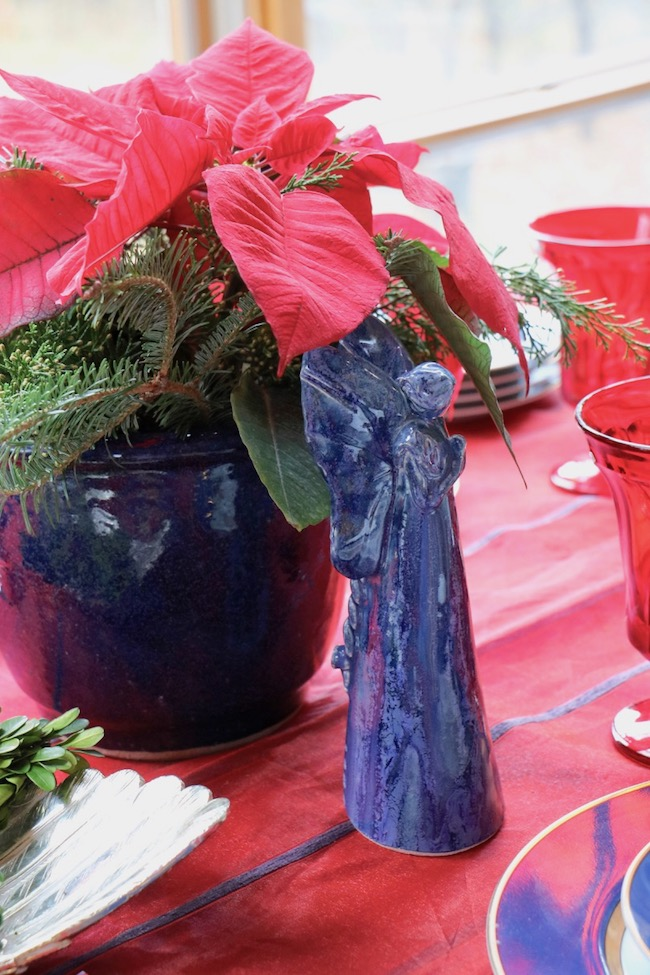 A handmade pottery angel in shades of navy is traditional Christmas decor in an unexpected color