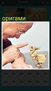 мужчина сделал оригами фигурку и рассматривает её, пытаясь с ней говорить