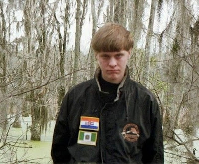 "Dylann Roof photographed ""proudly wearing a jacket with patches of the apartheid-era flags of South Africa and Rhodesia."""