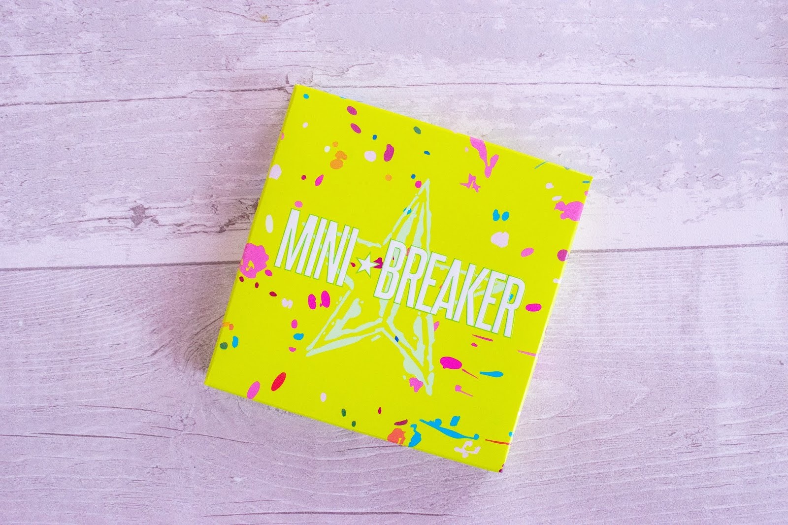A close up of the Jeffree Star Mini Breaker Palette packaging. The box is neon green with white and pink splats over it.