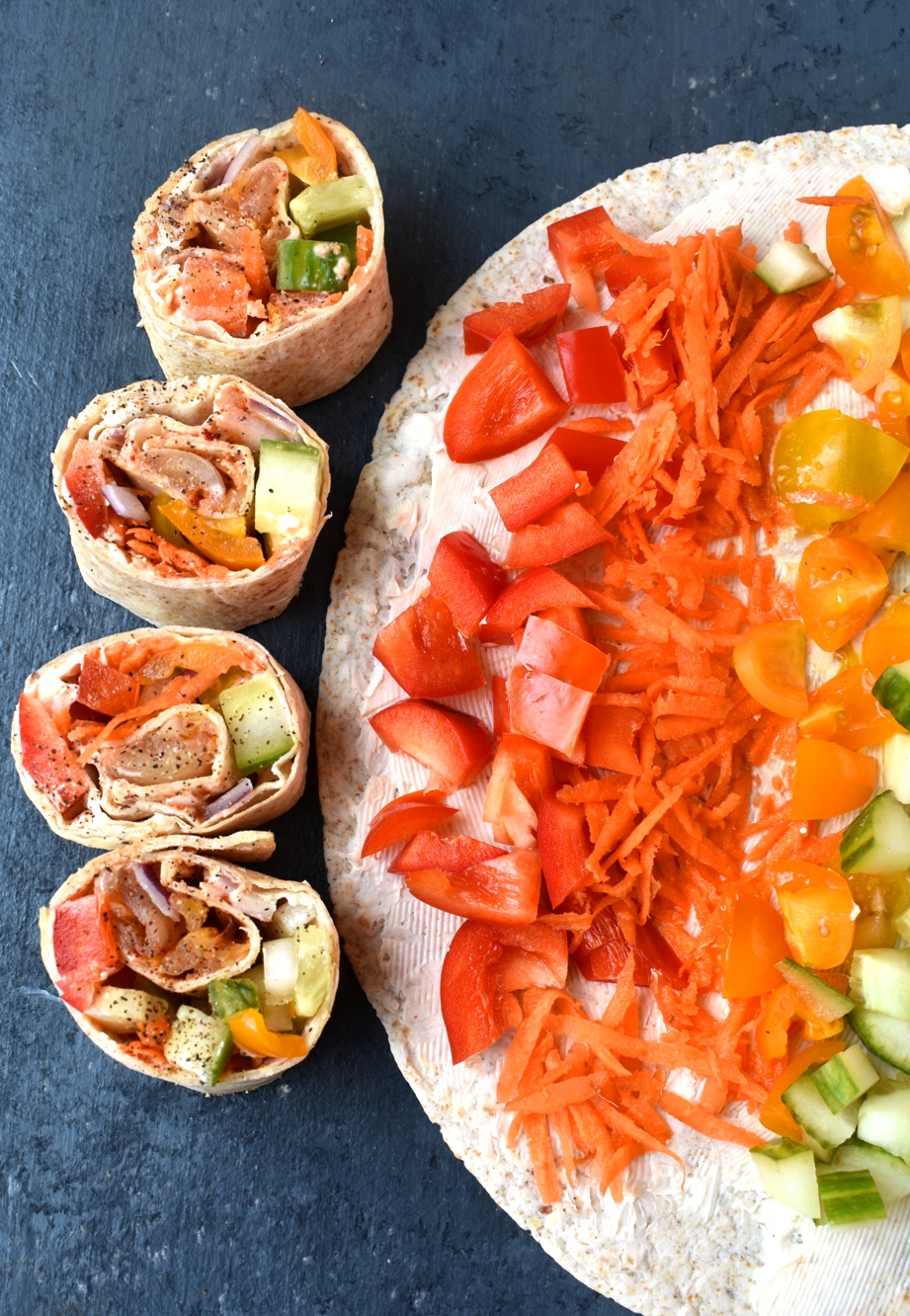 Rainbow Veggie Pinwheels are loaded with vegetable cream cheese, peppers, tomatoes, cucumber, red onion, carrots and kimchi on a whole-grain wrap. Perfect for entertaining, an easy appetizer or lunch!