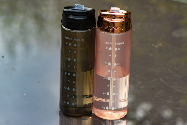 rose gold and black SMASH 700ml water bottles side by side on a glass table
