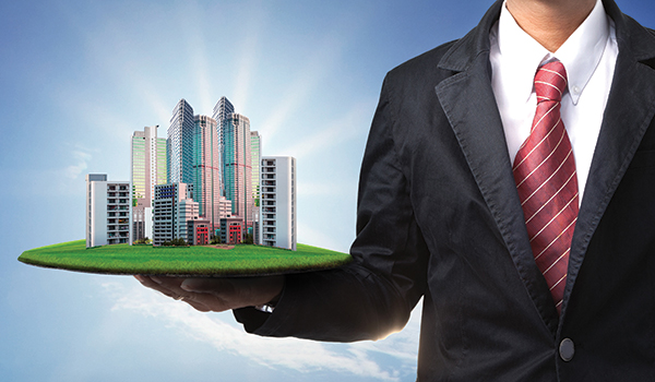 Image of A Business Man Showing A Building in his hands