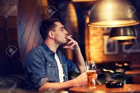 man smoking and drinking