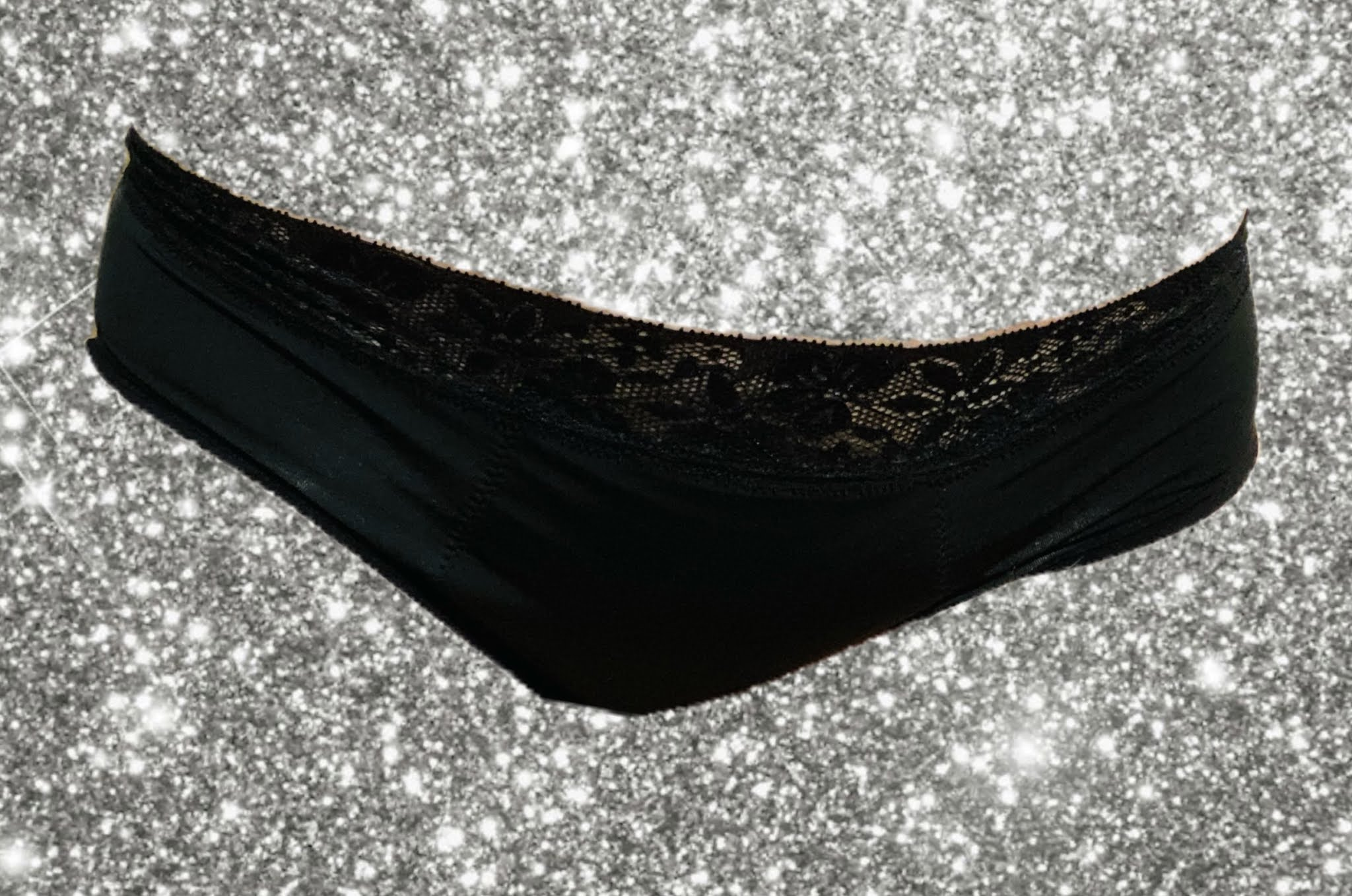 Cheeky wipes feeling pretty period pants in black with lace at the top against a silver sparkly backdrop