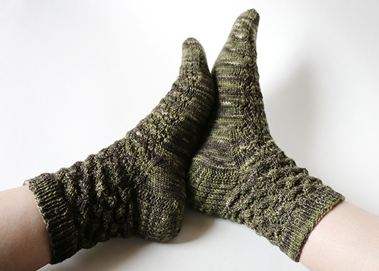 Feet with soles together wearing dark green hand-knit socks on white background