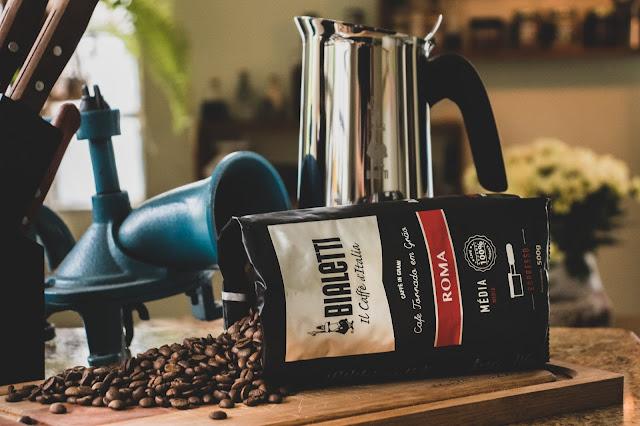 Café em grãos ao lado de moedor de café