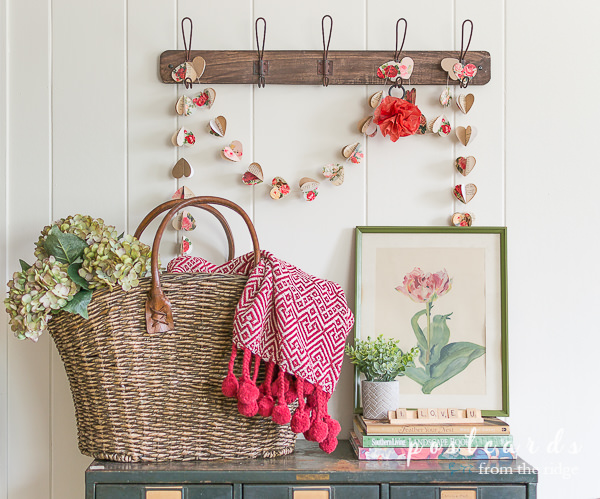 woven basket tote with faux hydrangeas and red throw blanket and paper heart garland