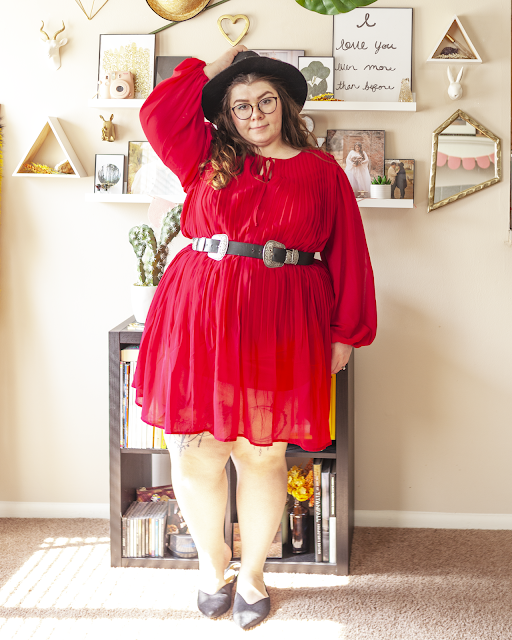 An outfit consisting of a black wide brim fedora, a red long sleeve midi dress with pleats and black pointed toe slingback flats.