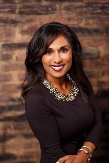 Image of a smiling woman with dark hair wearing a brown blouse and standing in front of a brick wall