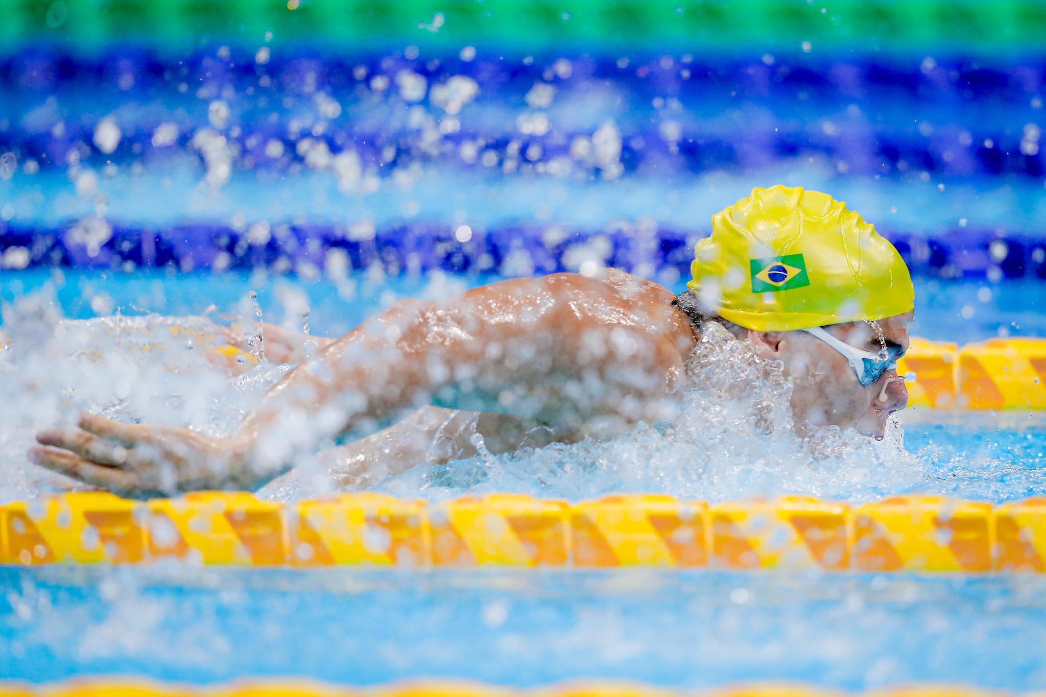Gabriel Bandeira faz o nado borboelta. Ele usa uma touca amarela e está com os braços para trás, acima da linha da água