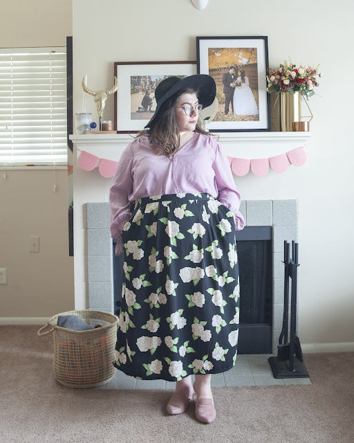 An outfit consisting of a black wide brim floppy hat, a lilac long sleeve wrap blouse tucked into a