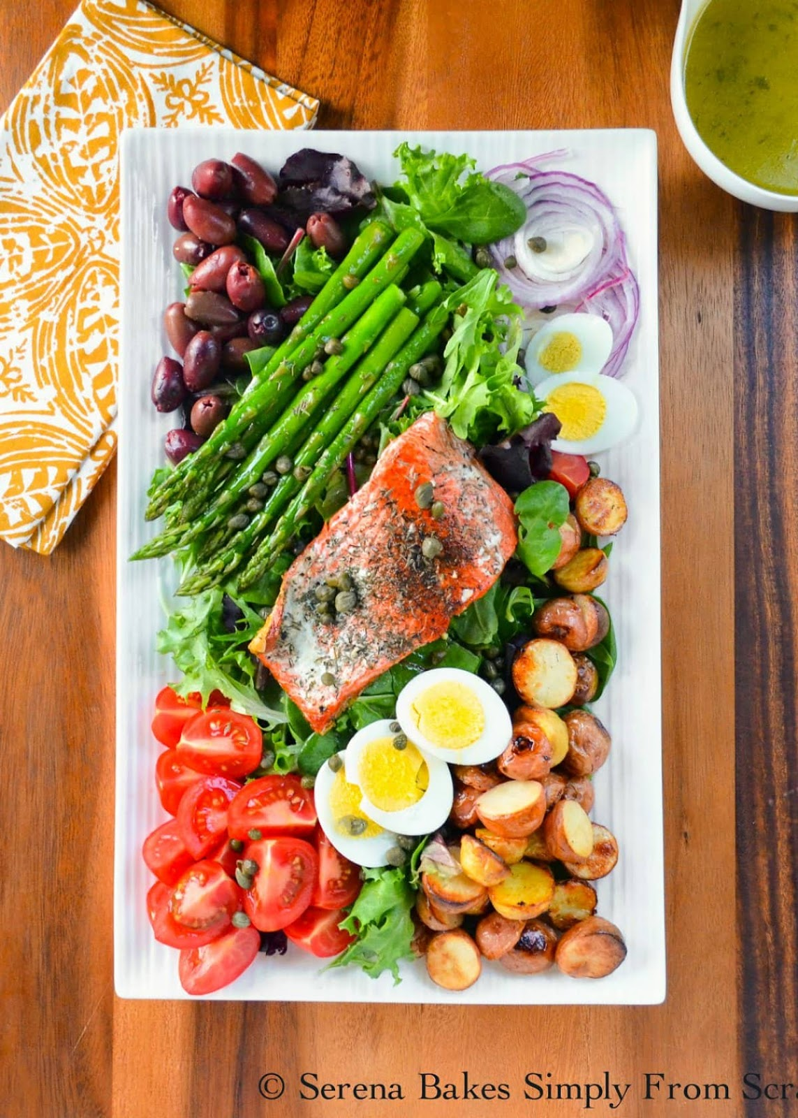 Salmon Nicoise Salad with lettuce, roasted potato, hard boiled eggs, sliced tomatoes, pan fried salmon, asparagus, kalamata olives, capers, drizzled with white balsamic lemon vinaigrette is a favorite easy healthy lunch or dinner recipe from Serena Bakes Simply From Scratch.