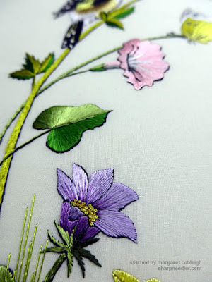 Three embroidered elements:pink flower, green leaf, and purple flower. Showing the reflective qualities of Piper's Silk.