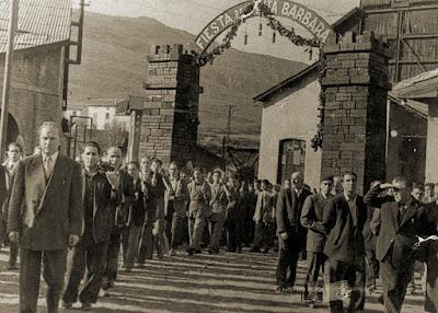 Procesión bajo el arco construido con briquetas en homenaje a Santa Bárbara (Barruelo, 1955)