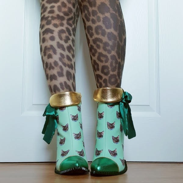 front wearing green ankle boots with quirky cat print and gold cuff