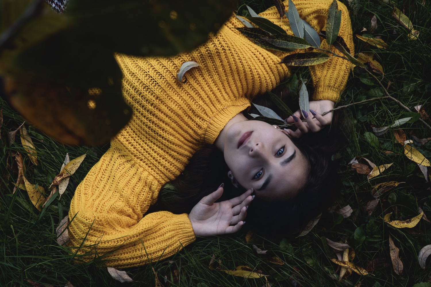 woman in sweater is laying on the grass
