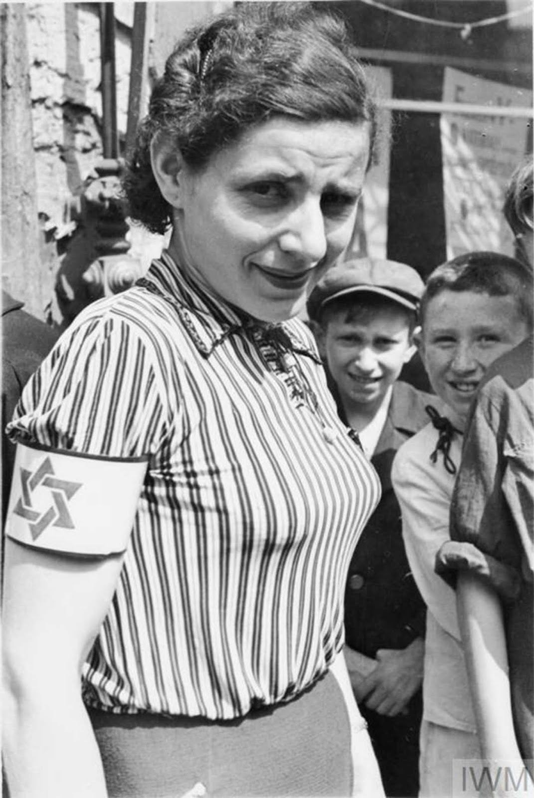 A portrait of a young woman wearing a striped blouse and an armband with the Star of David.